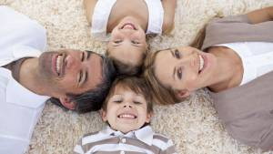 Family lying on floor with heads touching-Pandemic Impact On SW Florida Real Estate -Richardson Custom Homes-Fort Myers-300x169jpg