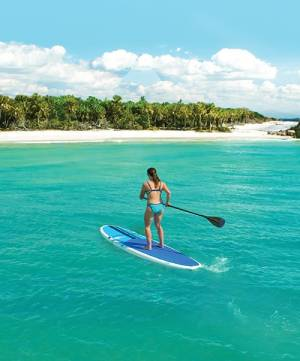 Girl paddle boarding on water-Pandemic Impact On SW Florida Real Estate -Richardson Custom Homes-Fort Myers-300x361jpg